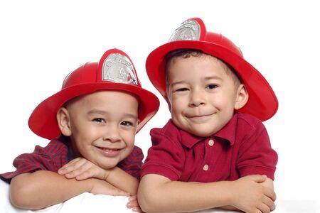 family life: Two Preschool Boys Wearing Firefighter Hats Stock Photo