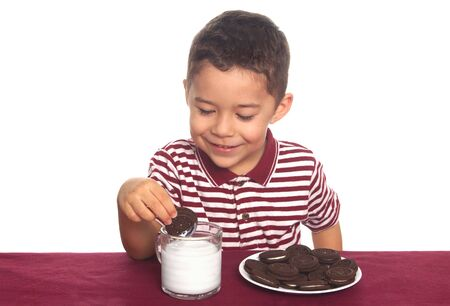 A young boy preparing to eat his chocolate cookies and drink his milk photo