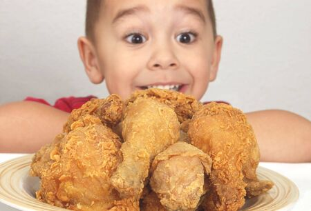 A plate of fresh fried chicken with a boy looking on (Focus is on the chicken)