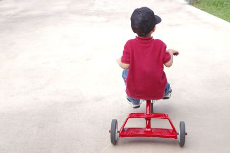 three wheeler: A young boy riding a classic red tricycle