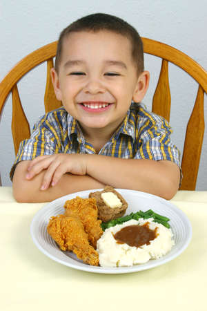 A happy young boy ready to eat his fried chicken dinner Stock Photo - 939110