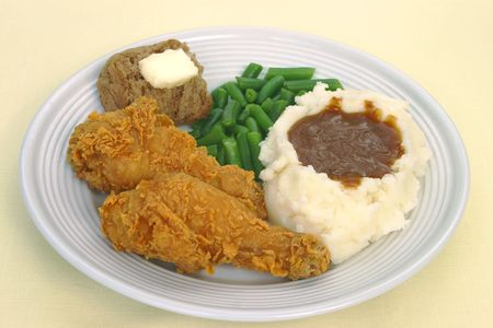A dinner of fried chicken,mashed potatoes with brown gravy,green beans,and a roll with butter
