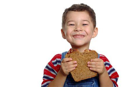 salopette: Gar�on avec le sandwich � beurre darachide sur le pain entier de bl� Banque d'images
