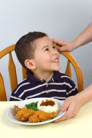 A young boy ready to eat his fried chicken dinner photo