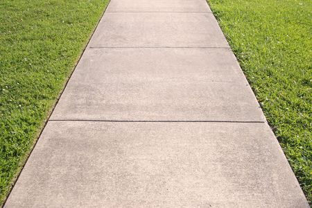 the sides: Abstract detail of a concrete sidewalk with grass on both sides Stock Photo