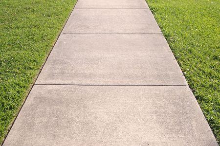 Abstract detail van een betonnen stoep met gras aan beide zijden
