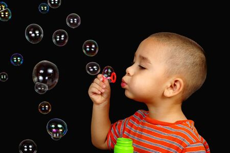 A boy blowing bubbles photo