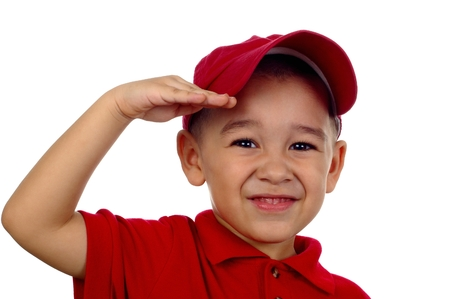 lighthearted: Portrait of a young boy saluting and smiling