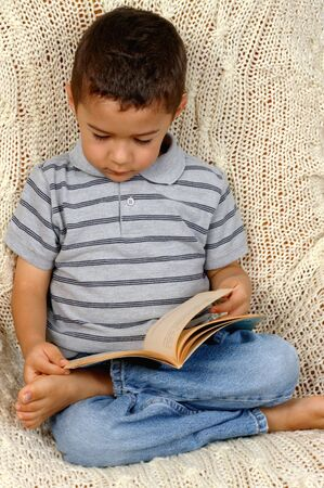 Boy reading a book, sitting on crocheted afghan blanket