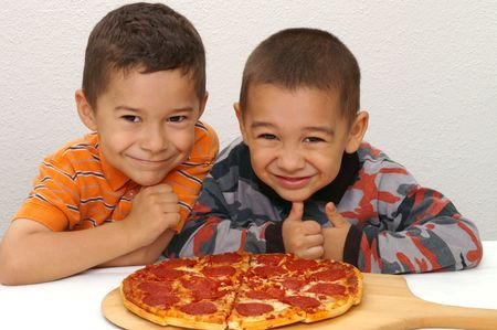 Two young brothers ready to eat a pepperoni pizza Banco de Imagens
