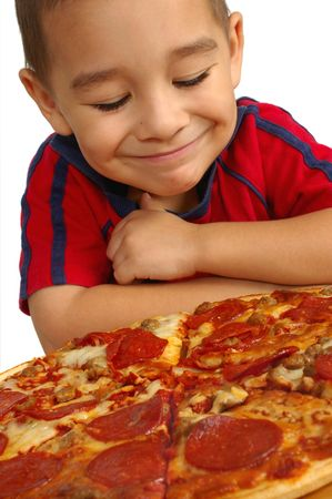Boy ready to eat a pepperoni and sausage pizza