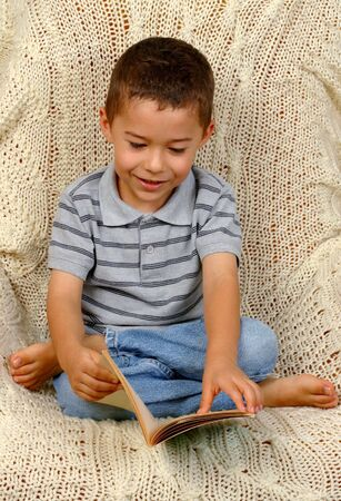 absorbed: Boy reading on a crocheted afghan blanket