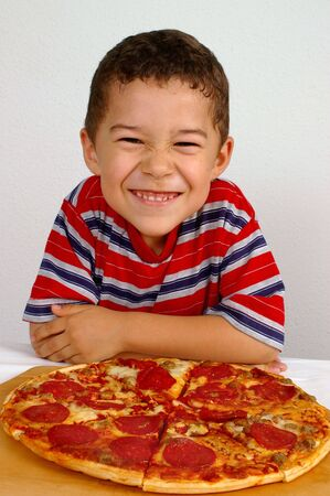 boy ready to eat a pepperoni and sausage pizza photo