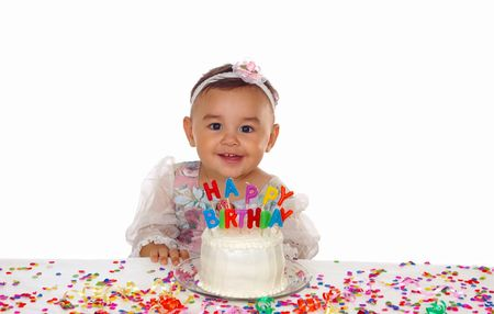 birthday party kids: Adorable baby girl smiles over a birthday cake with letter candles Stock Photo