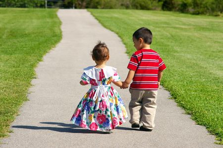Boy and  girl walking on a sidewalk photo