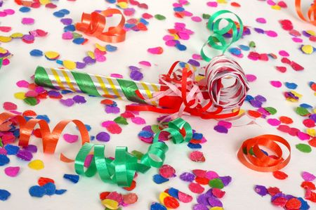 A party favor surrounded by confetti and ribbon streamers photo