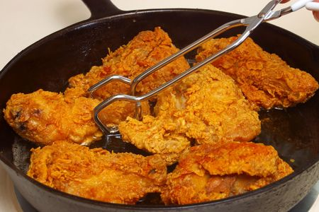 stovetop: fried chicken pieces cooking in a cast-iron skillet