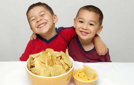 Two brothers ready to enjoy a huge bowl of tortilla chips and some queso Banco de Imagens