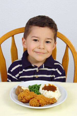 munch: Boy ready to eat his dinner of fried chicken with mashed potatoes, green beans, and a whole wheat roll Stock Photo