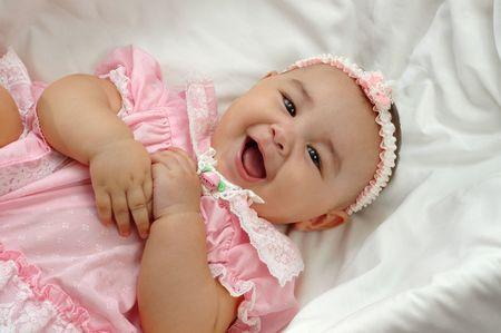 Cute baby girl laughing in a crib Standard-Bild
