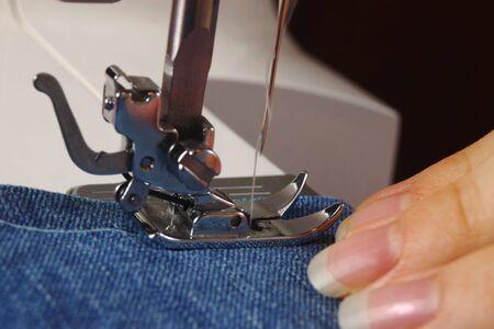 Using a sewing machine to stitch denim cloth
