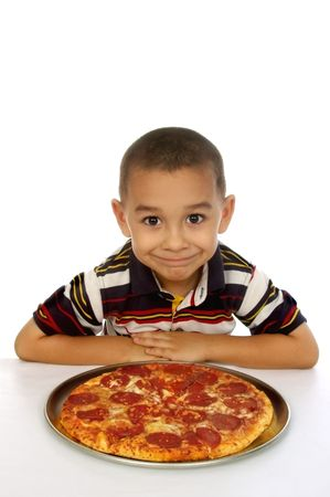 Hispanic boy ready to eat a pepperoni pizza photo