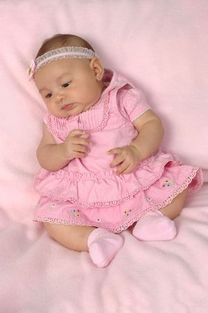 A 3-month-old baby girl in a pink dress Stock Photo