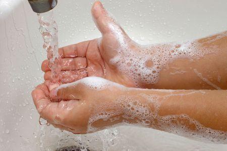 Niño lavándose las manos con agua corriente en un sumidero  Foto de archivo - 3410714
