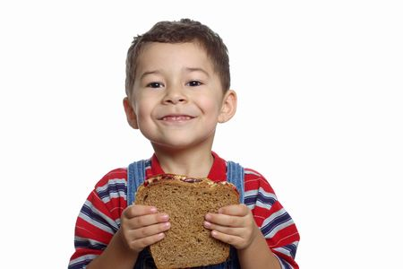 five-year-old boy holding peanut butter and jelly sandwich
