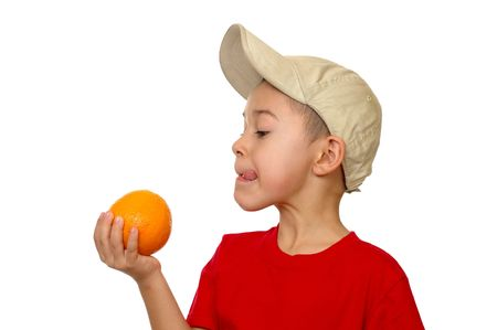 Seven-year-old boy with an orange, isolated on white