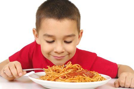 spaghetti saus: kind met een bord spaghetti en saus, op wit wordt geïsoleerd Stockfoto