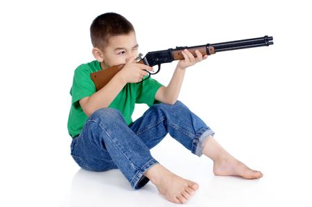 six-year-old boy aiming a toy rifle, in sitting position, isolated on white