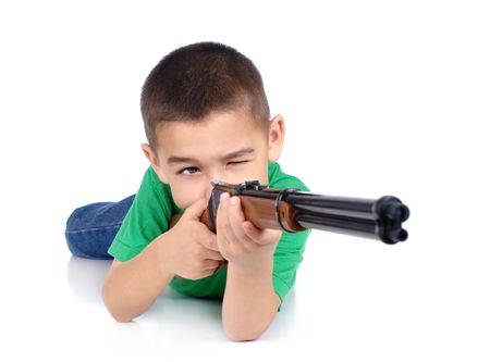 boy with toy rifle, in prone shooting position, isolated on white photo