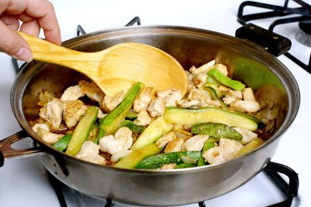 chicken and zucchini sauteeing in a frying pan