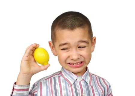 yuck: Boy holding a lemon and making a funny face Stock Photo