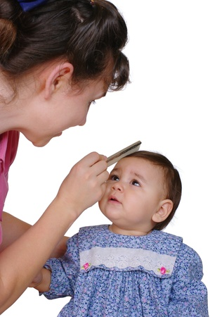 mixed race baby: Mother combing baby daughters hair