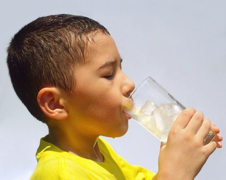 hete zweterige jongen slokjes limonade onder zware direct zonlicht Stockfoto