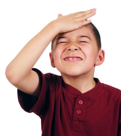 Acht-jarige jongen raakt zijn hoofd, teleurgesteld, geïsoleerd op witte achtergrond