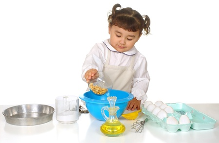 Cute three year old girl pouring peanuts in a bowl, with various baking ingredients and cooking utensils around her, on white background photo