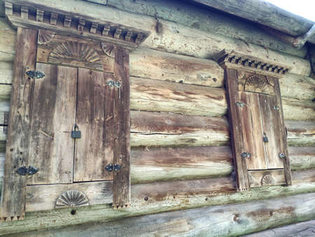 old wooden windows with carved shutters. windows with wooden architraves and shutters