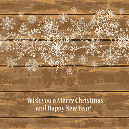 brown background: Christmas and New Year greeting card. Illustration with lacy ornate snowflakes on a wooden boards background