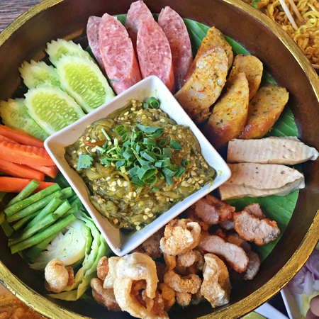 Khan tok or Khantoke, Thai food traditionally dinner include Green chilli dip, boiled vegetables, Thai spicy sausage, sour pork and Crispy Pork Skin