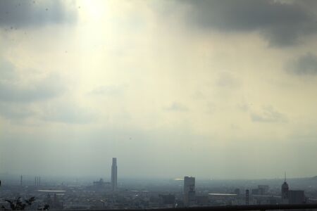 View of the city on a cloudy day with sun rays peeking out from the clouds Reklamní fotografie