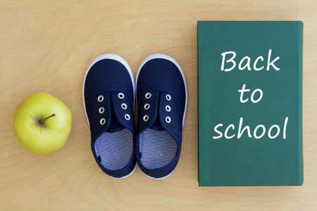 Back to school  Green book, blue shoes and green apple on a wooden table  photo
