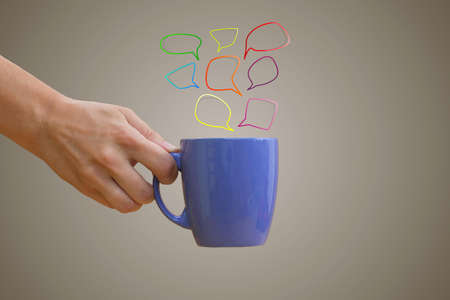 hand holding purple mug with hand-drawn multicolored speech bubbles photo