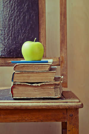 Green apple, blue pencil and old books on an old chair with vintage feel photo