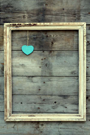 Vintage wooden frame with heart on a grunge background. Love design photo