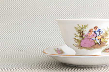 Vintage tea cup over background with  zigzags. Antique tea cup photo