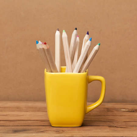 Color pencil in the cup on wooden background photo
