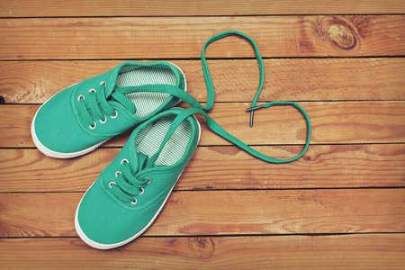 끈이 나무 바닥에 하트 모양을 만드는 신발 한 켤레의 상위 뷰입니다. 심장 신발 끈으로 만든 스톡 콘텐츠